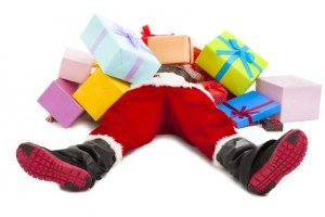 santa claus too tired to lie on floor with many gift boxes