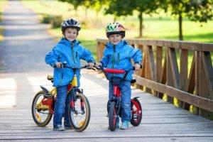 Two cute boys, siblings children, having fun on bikes in the par